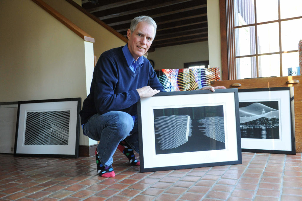 Visual artist Christopher Kennedy poses with pictures
